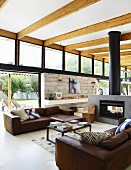 Brown leather sofas and coffee table in front of fireplace in open-plan interior with transom windows and wood-beamed ceiling