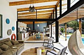 Lounge area with open sliding door in front of open-plan kitchen and dining area