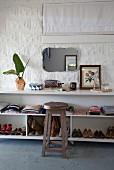 Holzhocker vor offenem Sideboard in Weiss mit Kleidung und Kinderschuhen