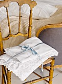 Lace-edged pillowcases tied with satin ribbon on wooden chair