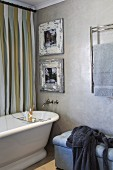 Pictures in vintage frames above retro bathtub next to upholstered bench and heated towel rack on marbled wall