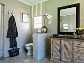 Toilet screened by half-height wall next to vintage, mango-wood washstand below black-framed mirror