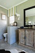 Vintage, mango-wood washstand with antique tap fittings and toilet behind half-height partition wall