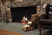 Kaminfeuer in ländlichem Ambiente mit Natursteinwand, seitlich Holzlager und restaurierter Ledersessel