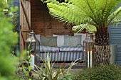 Sofa in wooden shed, two lanterns and tree fern in garden