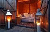 Large, lit candles in floor-standing candle lanterns outside wooden cabin with sofa in illuminated interior