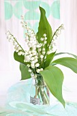 Posy of lily-of-the-valley in glass vase with vintage label