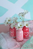 Small glass bottles painted with polka-dot hearts used as vases