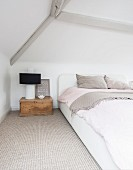 Lamp on vintage wooden trunk used as bedside table and double bed in minimalist attic conversion