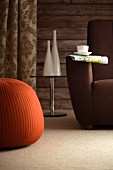 Brown armchair in front of rustic wooden wall, small glass side table and rust-red beanbag