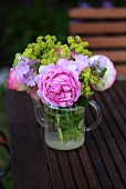 Posy of roses (variety ' Princess Alexandra'), mallow and lady's mantle in small, glass teapot