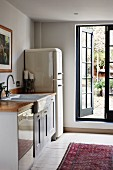 Simple kitchen counter and retro fridge-freezer next to open lattice door