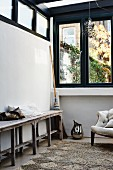 Rustic wooden bench against wall below strip of transom windows
