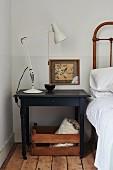 White retro table lamp on dark bedside table in corner of bedroom