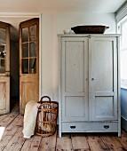 Schlichter Holzschrank und Korb im Zimmerecke, neben Flügeltür