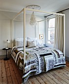 Patchwork cover on double bed with white-painted canopy frame in simple bedroom with wooden floor