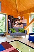 Designer sofa in corner of wood-panelled room with glass floor