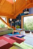 Holzvertäfelter Wohnraum in zeitgenössischer Architektur, Patchworkteppich auf verglastem Bodenbereich