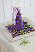 Purple felt Christmas tree on plate with purple gravel and green baubles