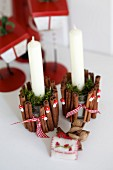 Festive, glass candle holders decorated with cinnamon sticks, ornamental toadstools and moss