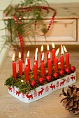 Festive arrangement of red candles and baubles
