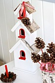 Red and white bird box decorated with ribbons & pine cones; Christmas arrangement