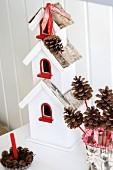 Rot-weisses Vogelhäuschen verziert mit Schleifen & Zapfen als Weihnachtsschmuck