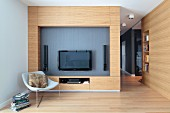 Designer armchair in front of wooden living room wall with flatscreen TV and speakers in niche in open-plan interior