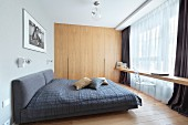 Dark grey double bed, floating wooden counter in front of window and wooden fitted wardrobes in bedroom