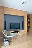 Designer armchair in front of wooden living room wall with flatscreen TV and speakers in niche in open-plan living room