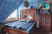 Bed with carved wooden frame and Oriental-style headboard in attic room with mottled blue walls