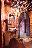Washstand made from rustic hand pump against brick wall; arched, Medieval-style doorway