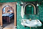 Sink on green, sponged wall next to open door with carved wooden frame and view into bedroom
