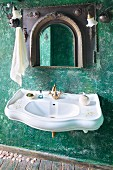 Curved sink with vintage brass taps and mirror with Oriental-style frame on green wall