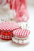 Pin cushions hand-crafted from empty ribbon reels, fabric scraps and odds and ends of trim