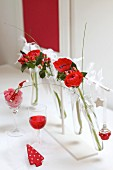 Christmas table arrangement of red flowers in test tubes in white frame