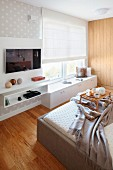 Double bed opposite fitted cabinets below window, wall mounted shelves and flatscreen TV in modern bedroom