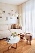 Runder Beistelltisch und Hocker mit Fellbezug auf Sitzpolster in heller Wohnzimmerecke