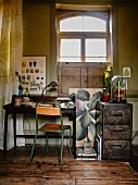 Simple chair with green-painted metal frame at writing desk next to metal filing cabinet below window in vintage interior