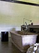 Steinbadewanne in schlichtem Badezimmer mit Betonwänden und Betonboden