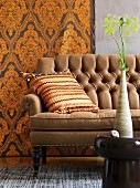 African ceramic vase on stool, ethnic scatter cushion on antique sofa and wallpaper with majestic pattern