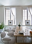 Contemporary chairs with white covers around wooden table in front of lattice window