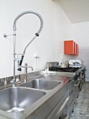 Stainless steel kitchen counter with contemporary pull-out spray tap in loft-style kitchen