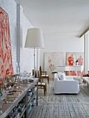 Edelstahlregal mit Besteck und Geschirr, im Hintergrund Sofa mit weisser Husse und Klavier in offenem Wohnbereich mit geweisselter Ziegelwand