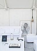 Sofa und Polsterhocker mit weisser Husse um Couchtisch im Wohnbereich mit geweisselter Ziegelwand