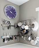 Kitchen utensils and clock hung on walls painted pale grey