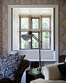 Table lamp on side table between seating in front of lattice window with open interior shutters