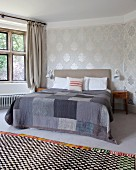 Checked rug in front of double bed with patchwork blanket in various shades of grey in traditional bedroom