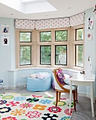 Brightly patterned rug in front of comfortable beanbag in window bay and antique chair at white table to one side in teenager's bedroom