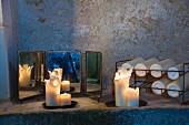 Lit pillar candles and small three-winged mirror next to metal rack of candles on stone shelf